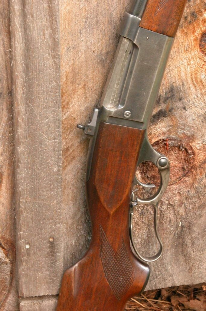 rifle leaning against a slab of wood