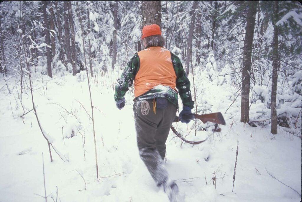 hunter in orange walking through snowy woods
