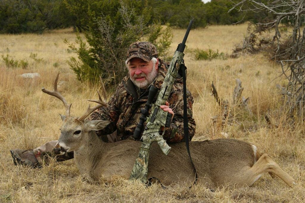 hunter with a cull buck and a remington rifle
