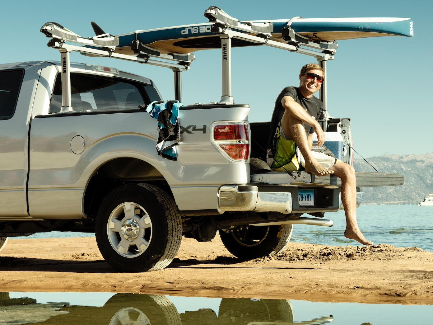 Guy sitting on the back of a pick-up truck with surfboard on rack.
