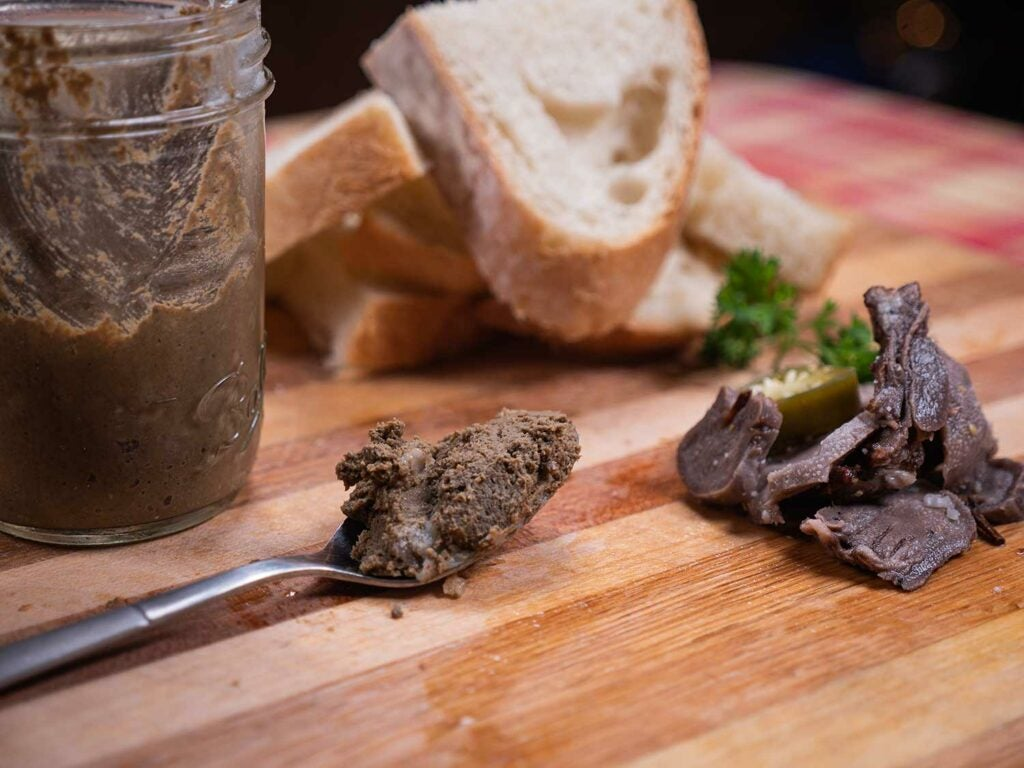 venison liver pate on a wooden cutting board.