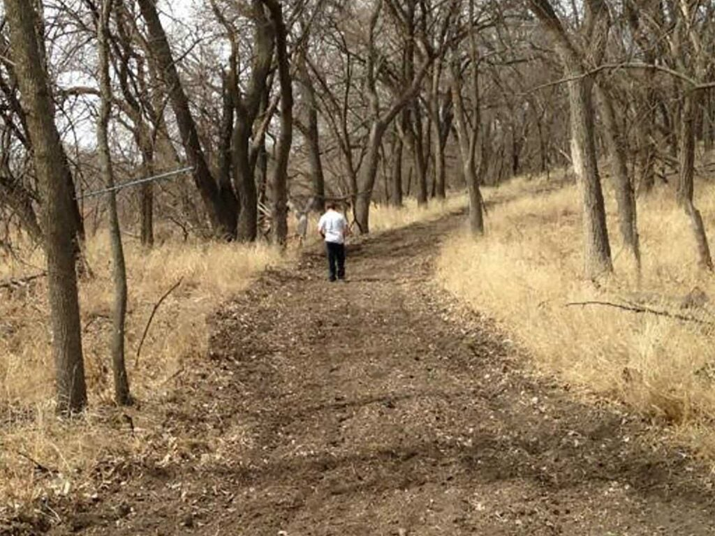 a hunter walking on a deer path for a food plot.