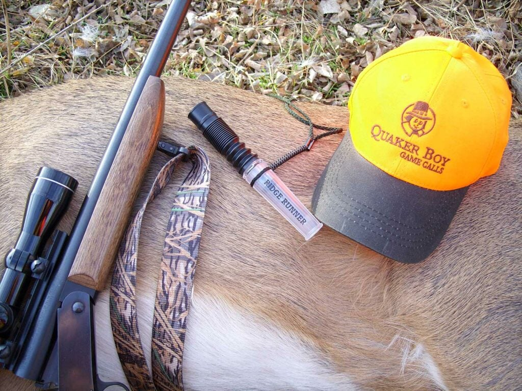 a quaker boy hat on a deer with hunting rifle and call