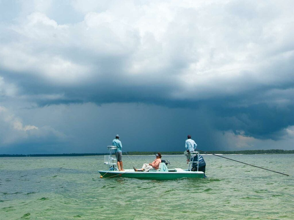 Anglers fishing on a boat with stormy sky.