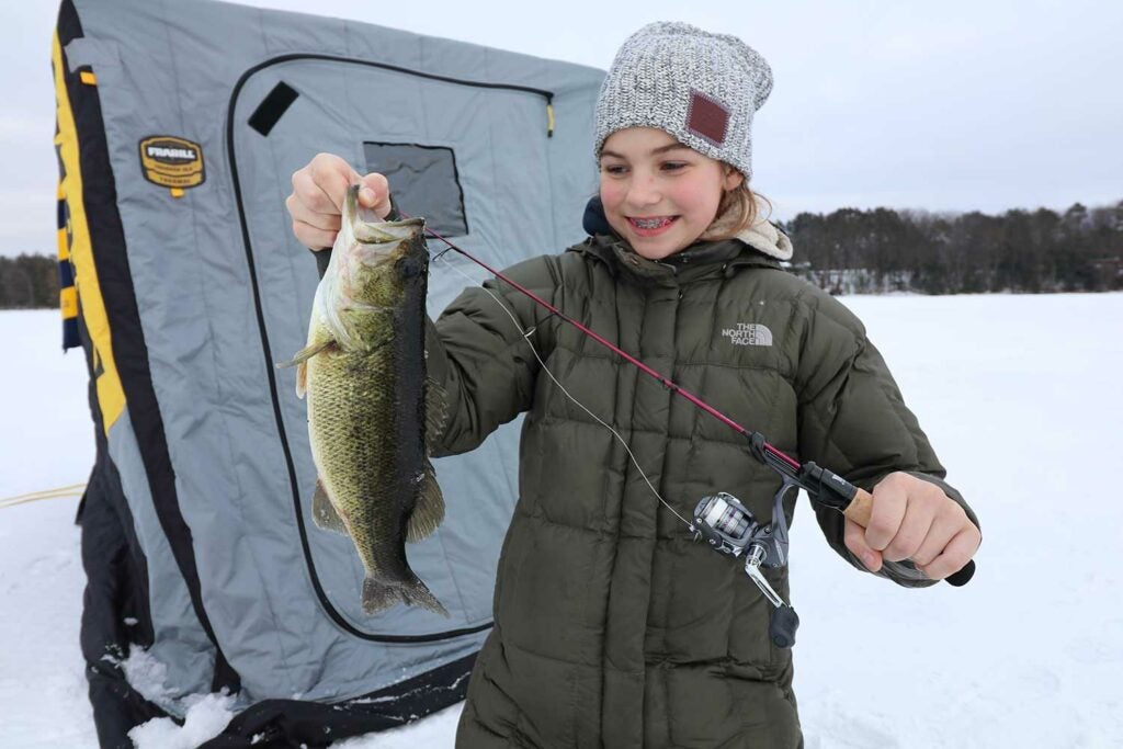 Young girl holding up fish in snow