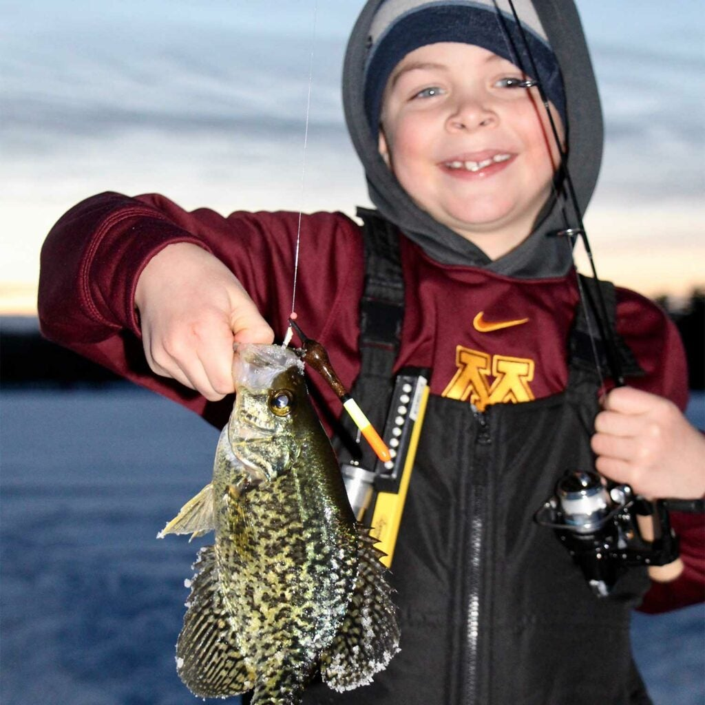 Young child holding up a fish caught from ice fishing.