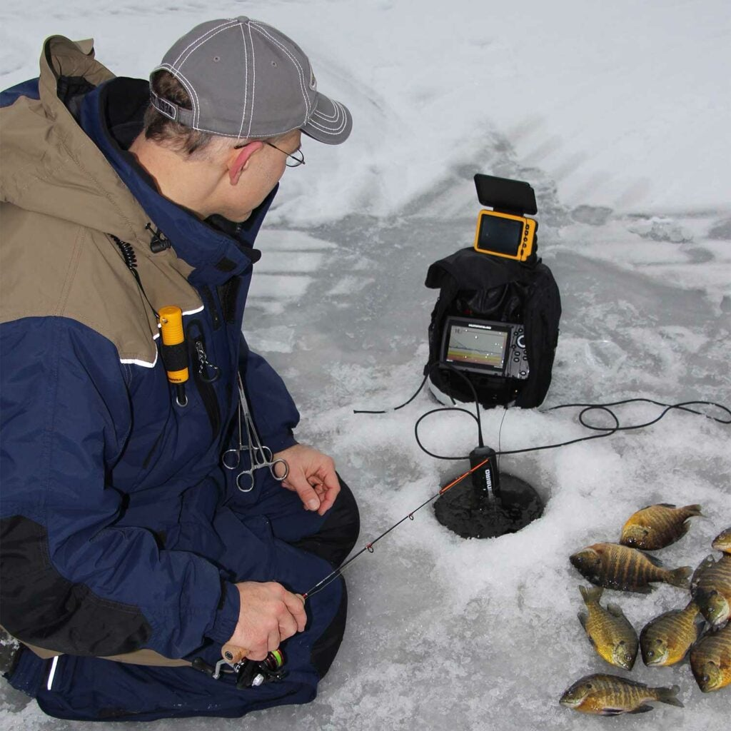 Angler using CHIRP sonar for ice fishing.