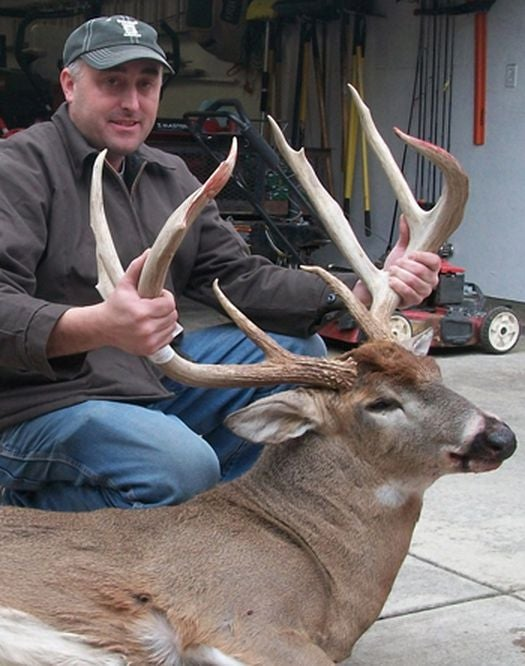 hunter with a 9-point trophy buck