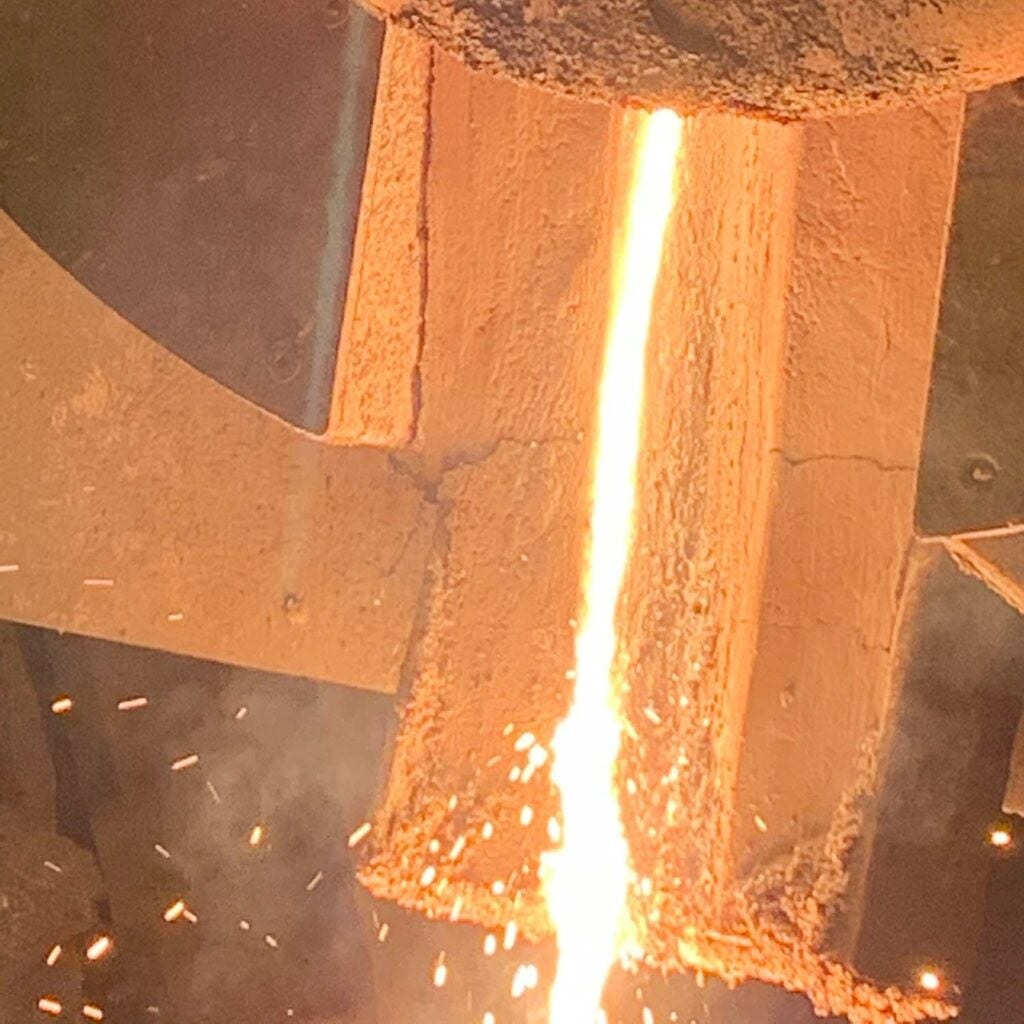 Molten metal being poured from the induction furnace into the tundish, a trough through which molten metal flows under vacuum (not shown).