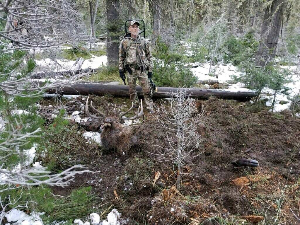 Hunter standing beside hunt that has been buried by grizzly bear.