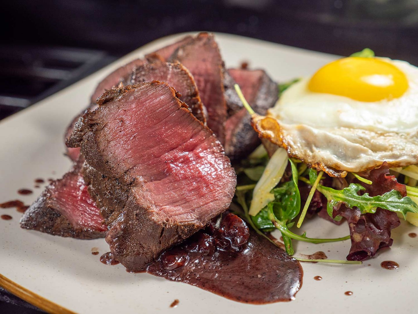 A perfectly cooked venison backstrap with a dried cherry reduction, arugula salad, and a fried egg.