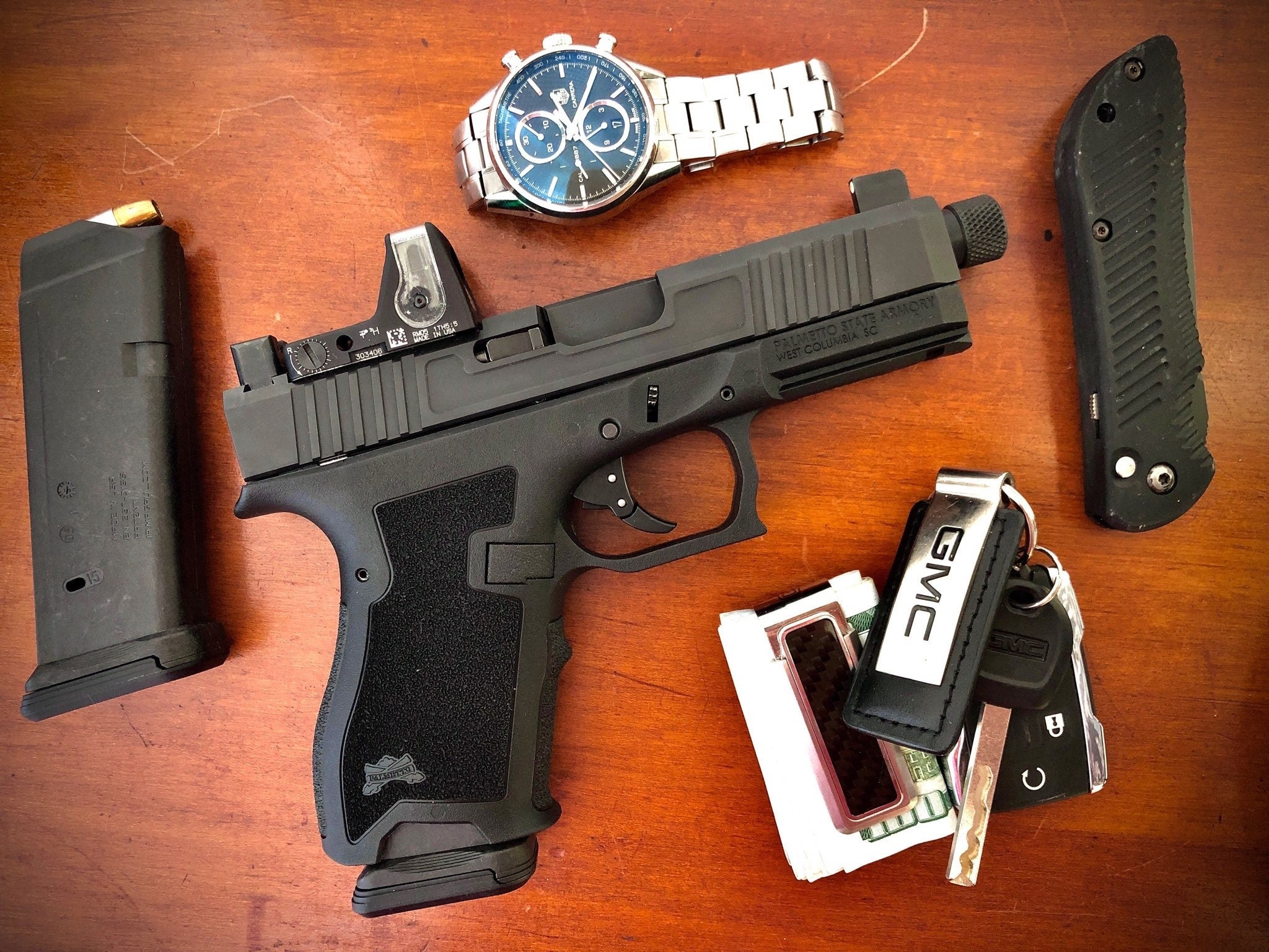 Handgun on table with keys watch and knife.