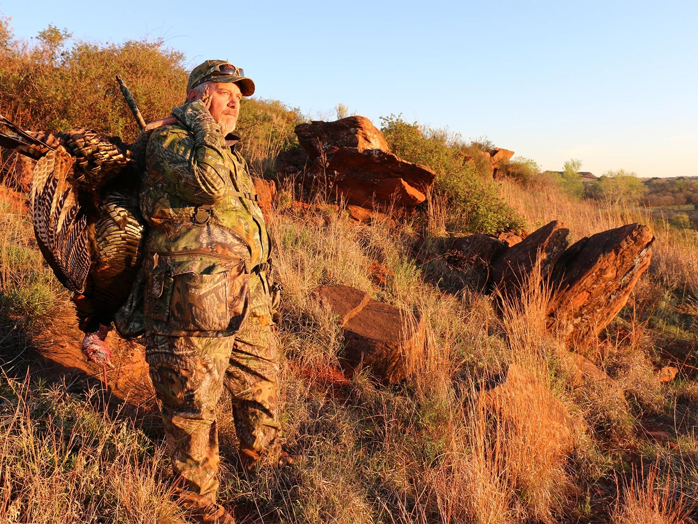 Turkey hunter on a hillside at sunset.