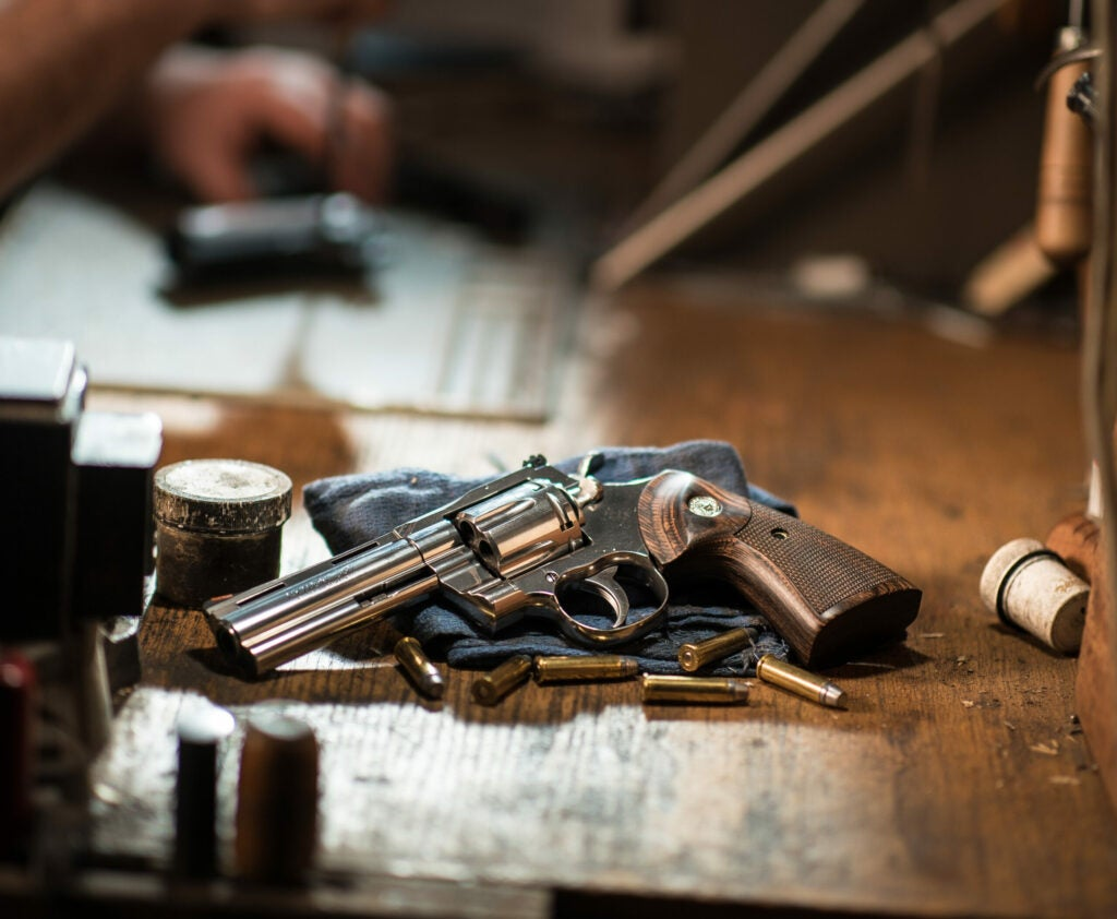 Double-action Colt revolver on a workbench.
