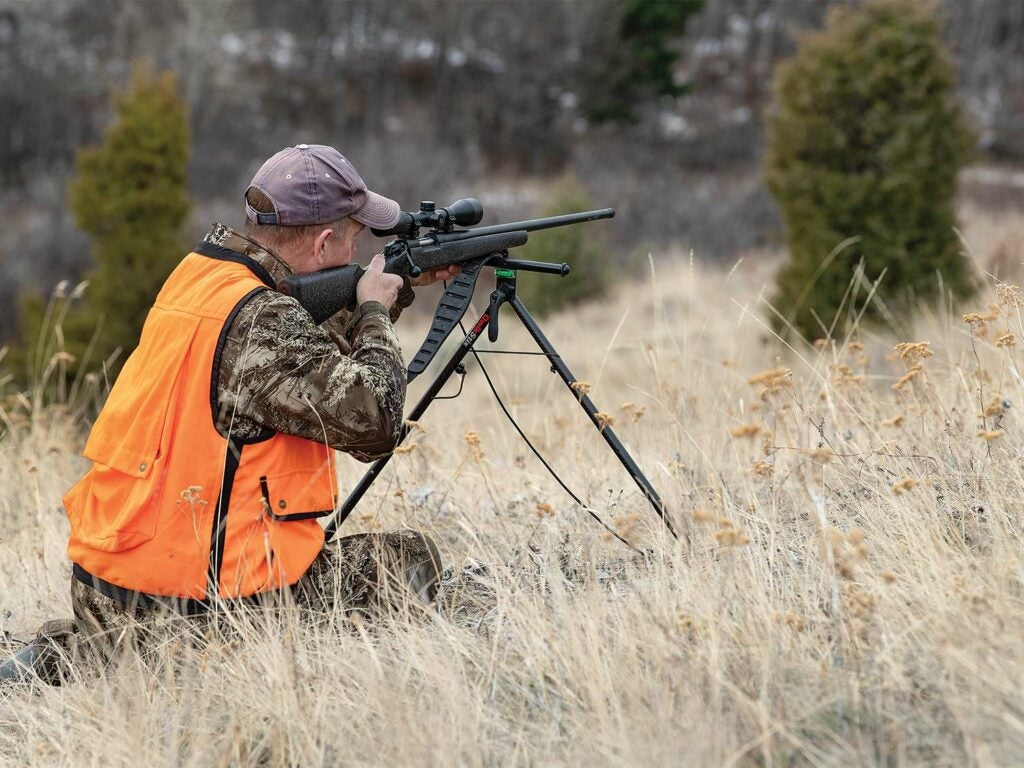 Hunter aiming a rifle with a bipod.
