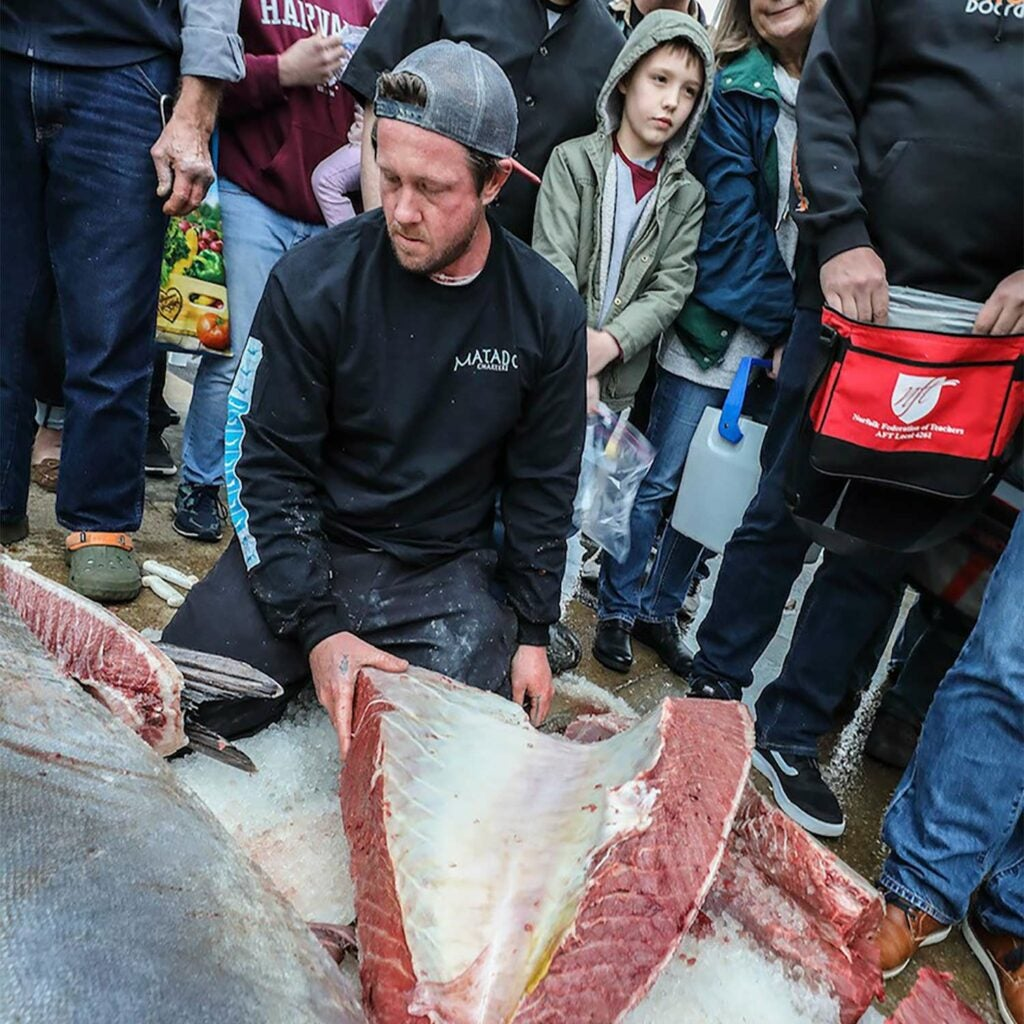 Man carving bluefin tuna steaks.