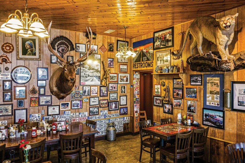 The interior of a diner with pictures and taxidermy on the walls.