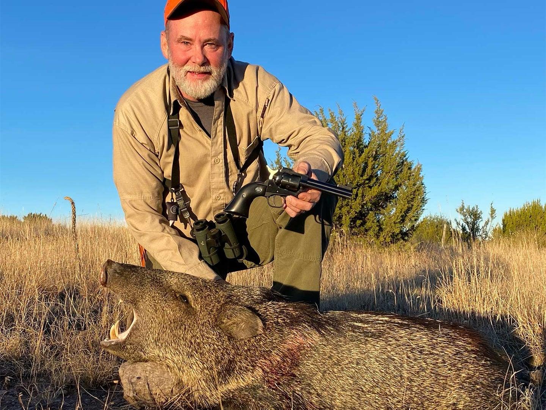Hunter kneeling behind a wild pig.