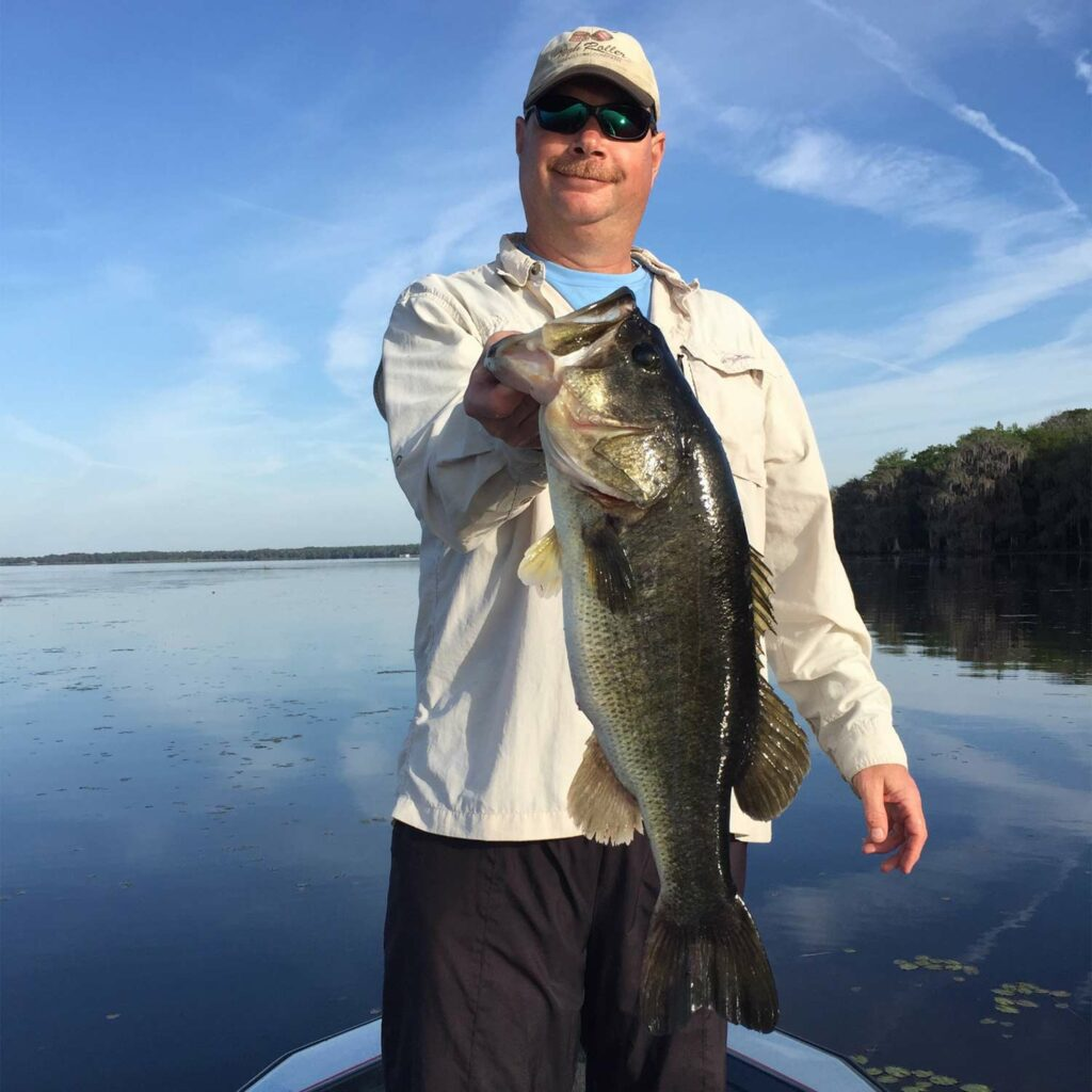 Angler holding up a largemouth bass.