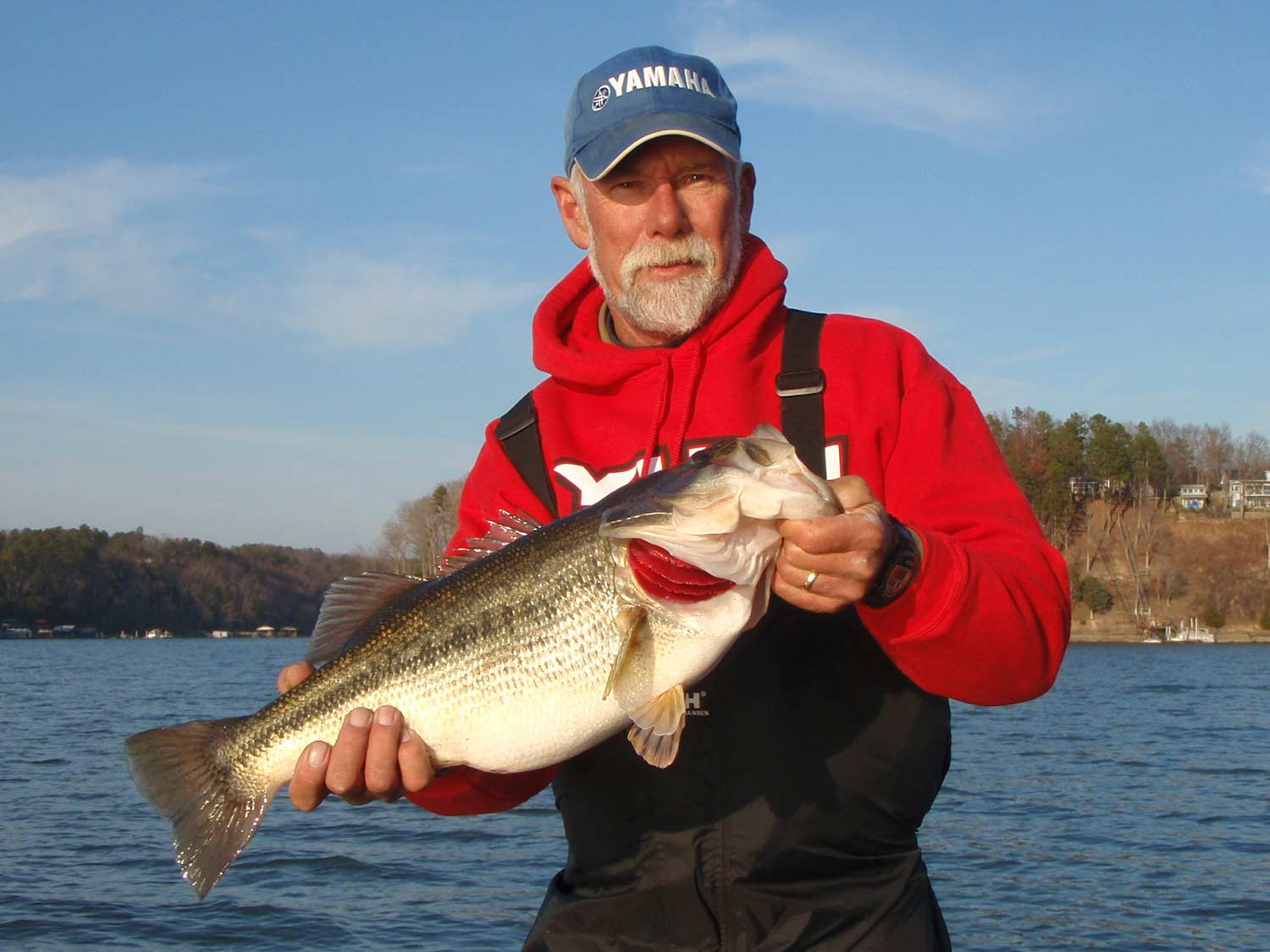 An angler in red holding a largemouth bass.