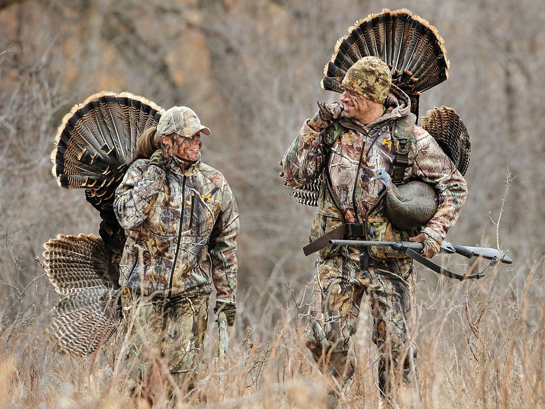 Two turkey hunters walking through a field.