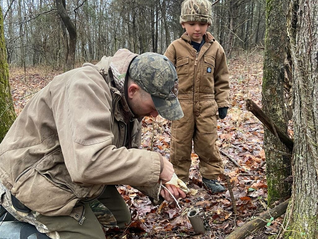 The author and his son bait a Duke Dog Proof raccoon trap.