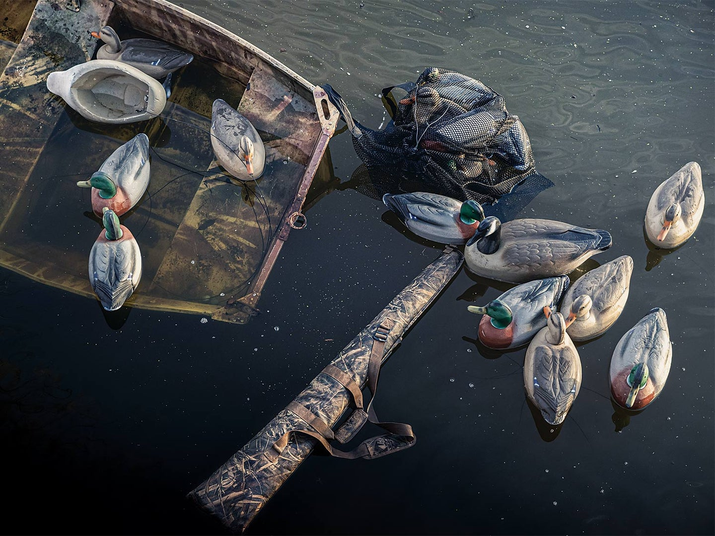 A capsized rowboat with duck decoys and gun case.