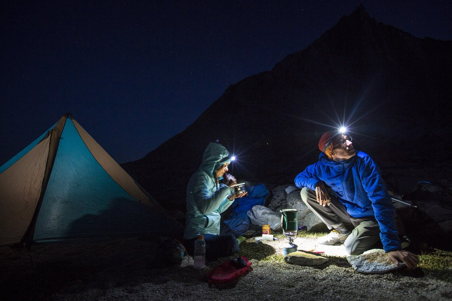 Campers using Black Diamond Headlamps at a campsite at night.
