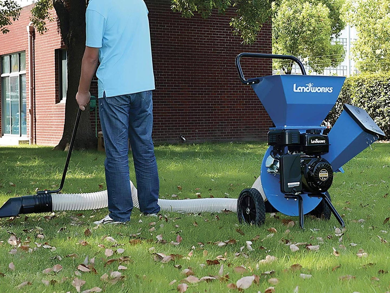 Man using a blue woodchipper.