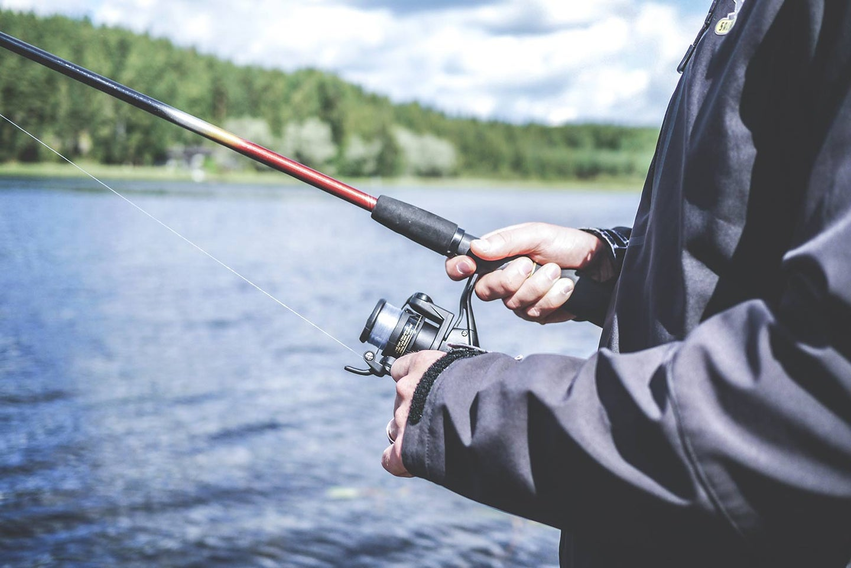 Angler with a fishing reel at a lake.