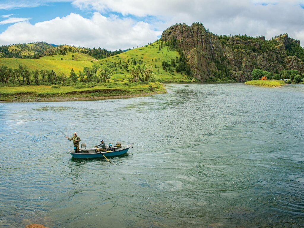 To anglers in a boat on a river.