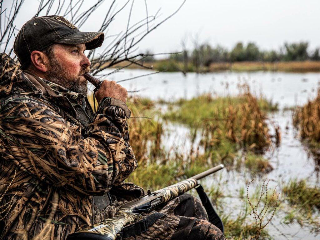 Hunter calling in ducks on a lake.