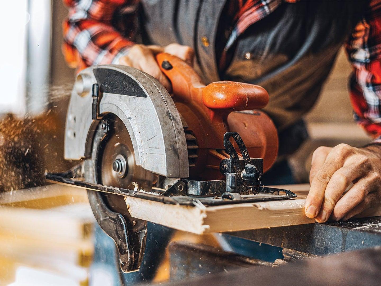 Carpenter cutting plank by circular saw
