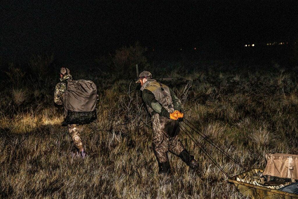 Hunters hauling duck hunting gear at night.