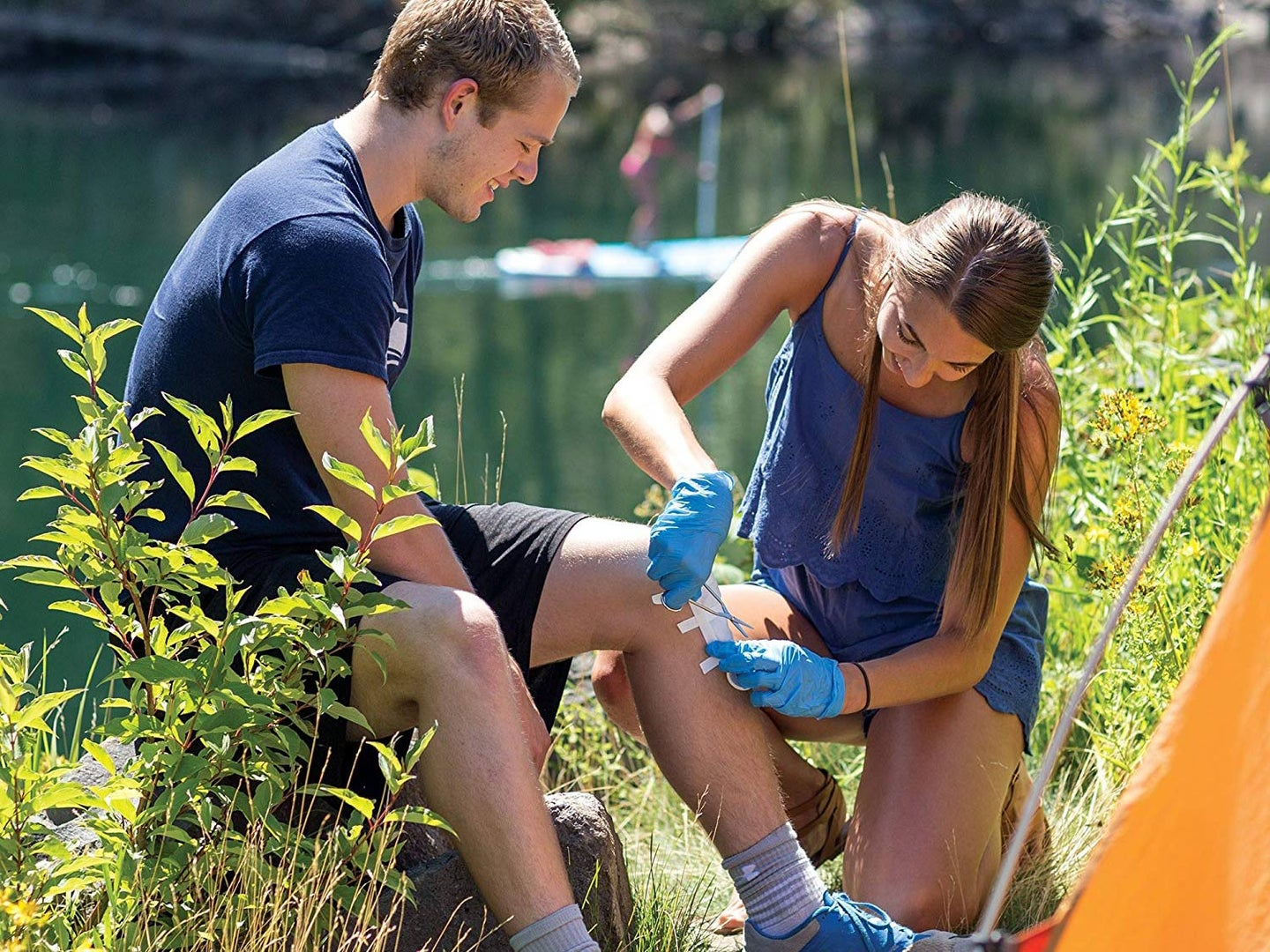 Woman administering first aid to a man's knee.