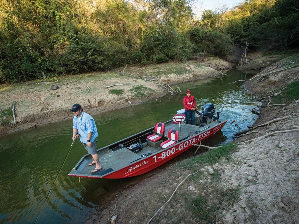 Anglers in a small boat on a creek.