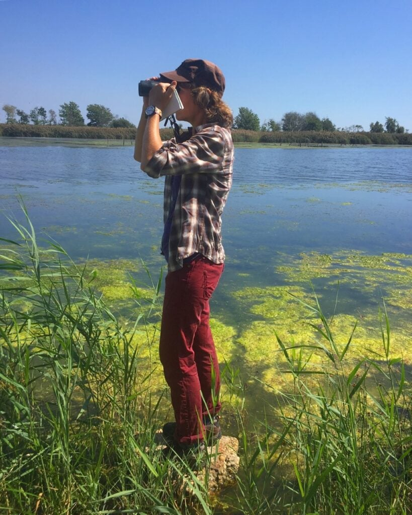 a person standing by a body of water using binoculars to look for birds