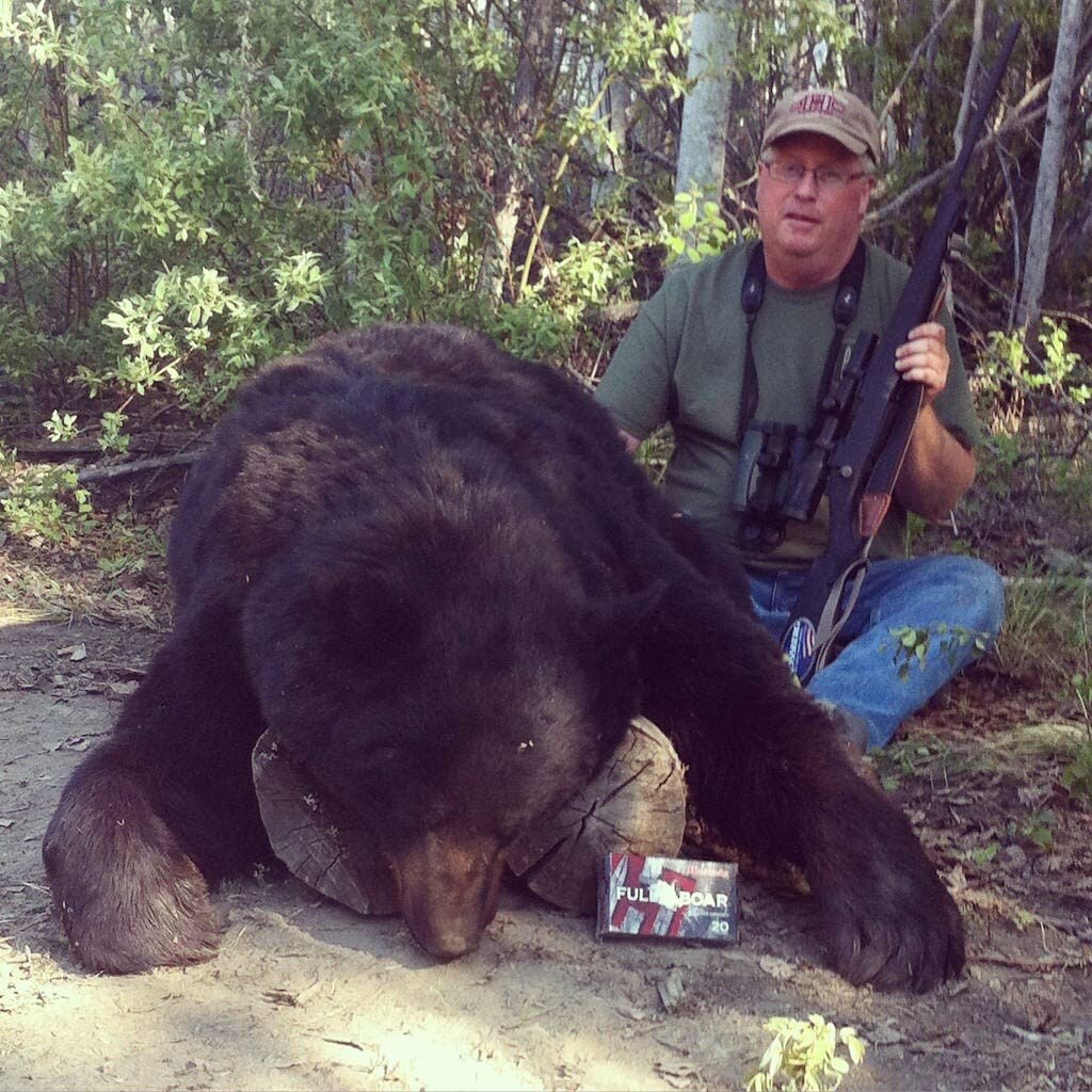 Hunter with a large black bear.