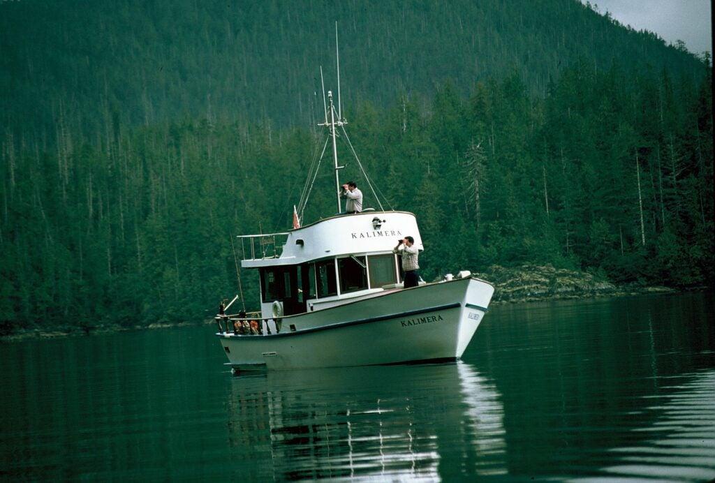 Men on boat with binoculars.