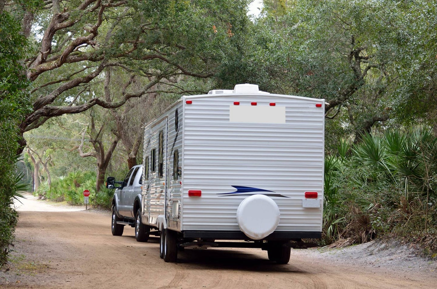 A camper being pulled behind a truck.