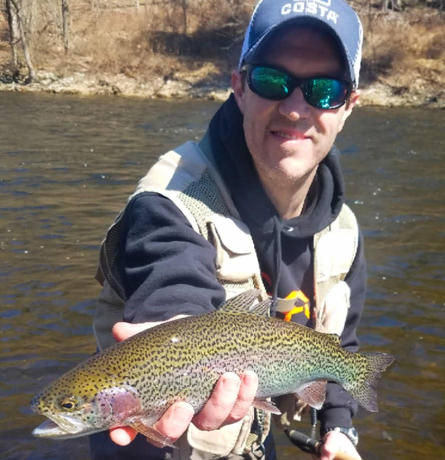 Matt Wettish holding up a rainbow trout.