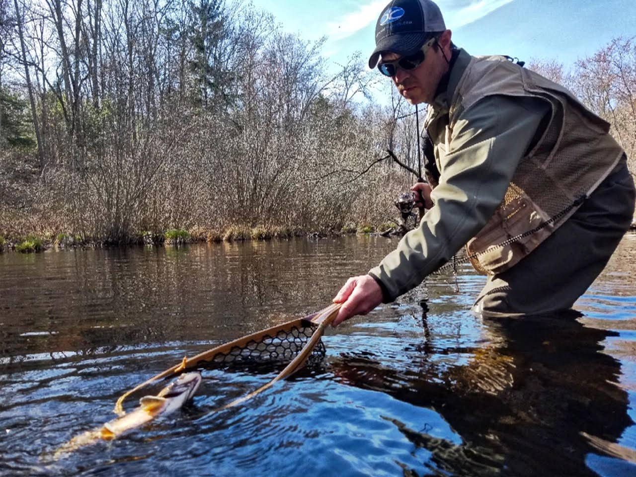 Angler using a net to pull in a fish.