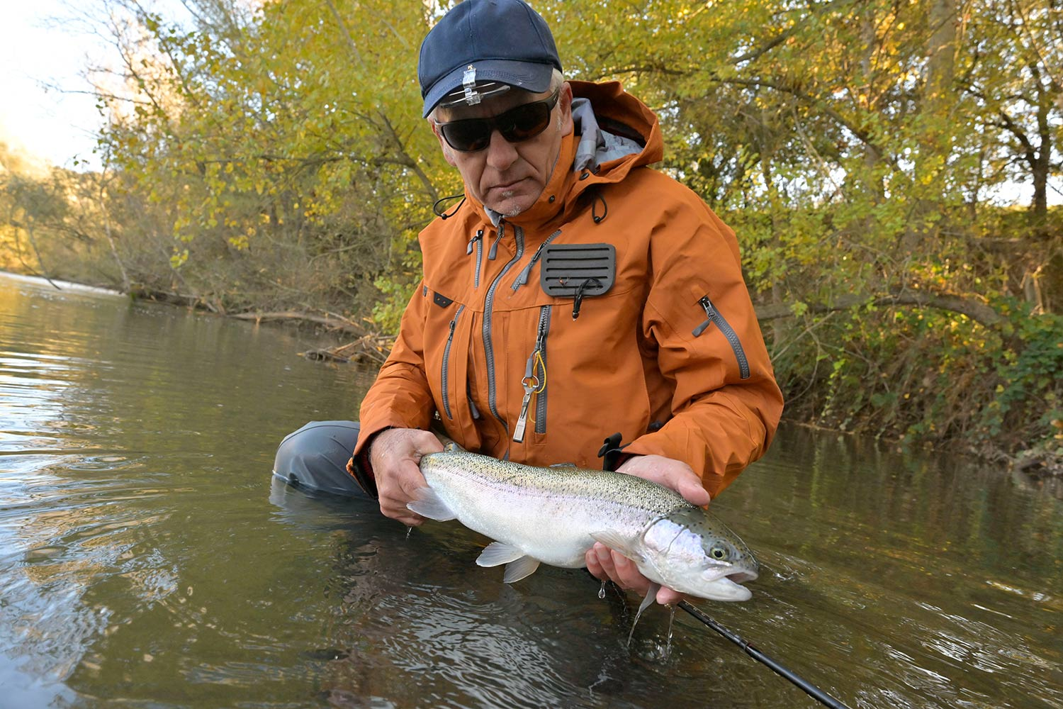 An angler with a large rainbow trout.