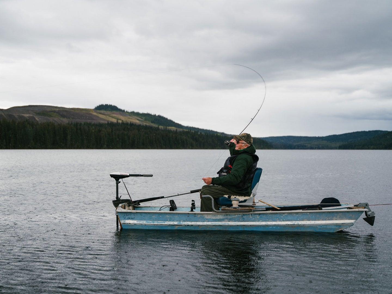 Man fishing in lake while wearing life jacket