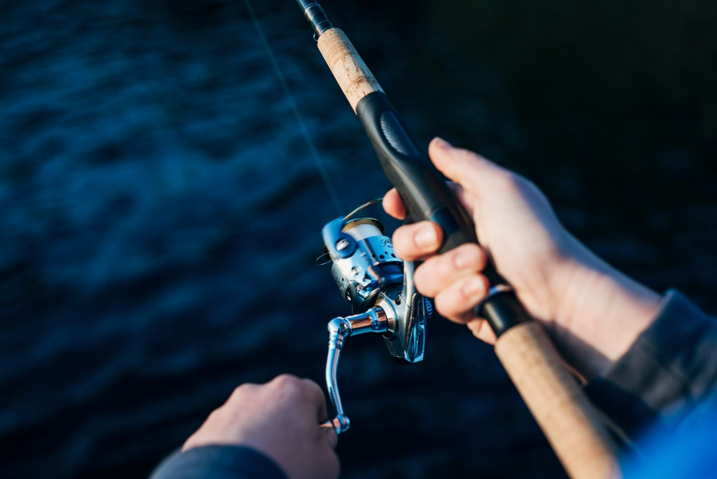 Holding and reeling a fishing pole.