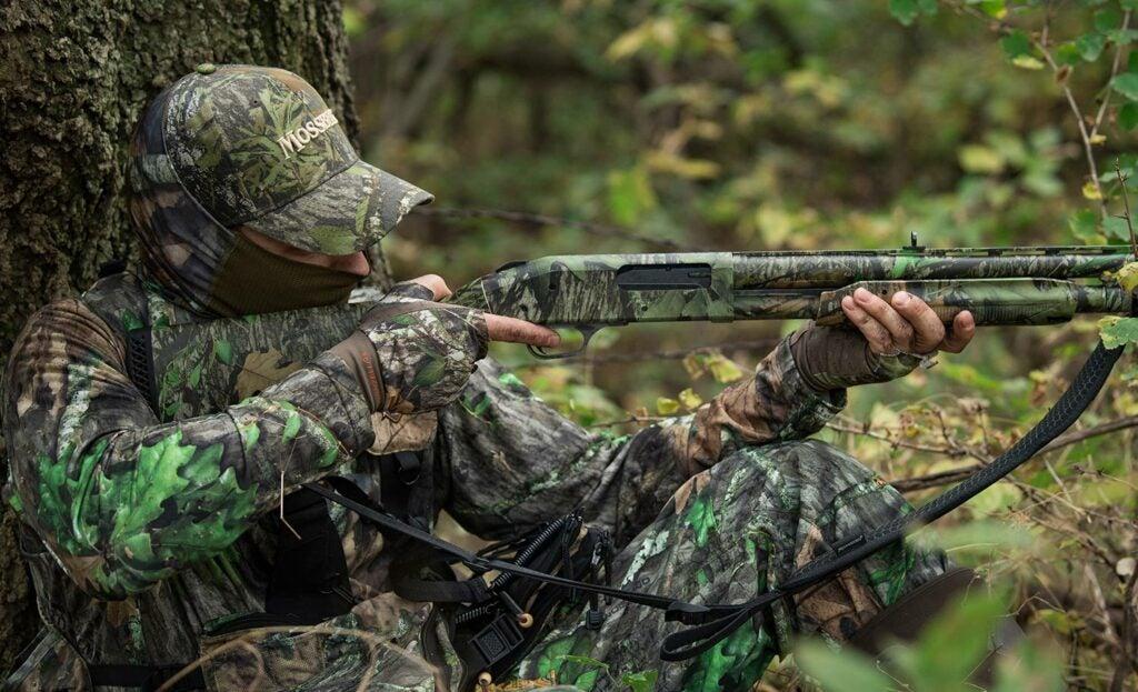 Hunter aiming a Mossberg shotgun.