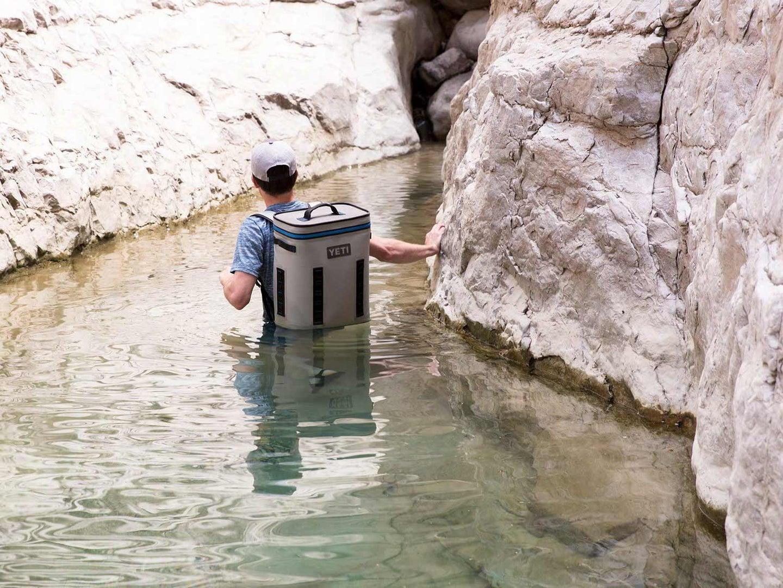 Man walking through a lake into a cave