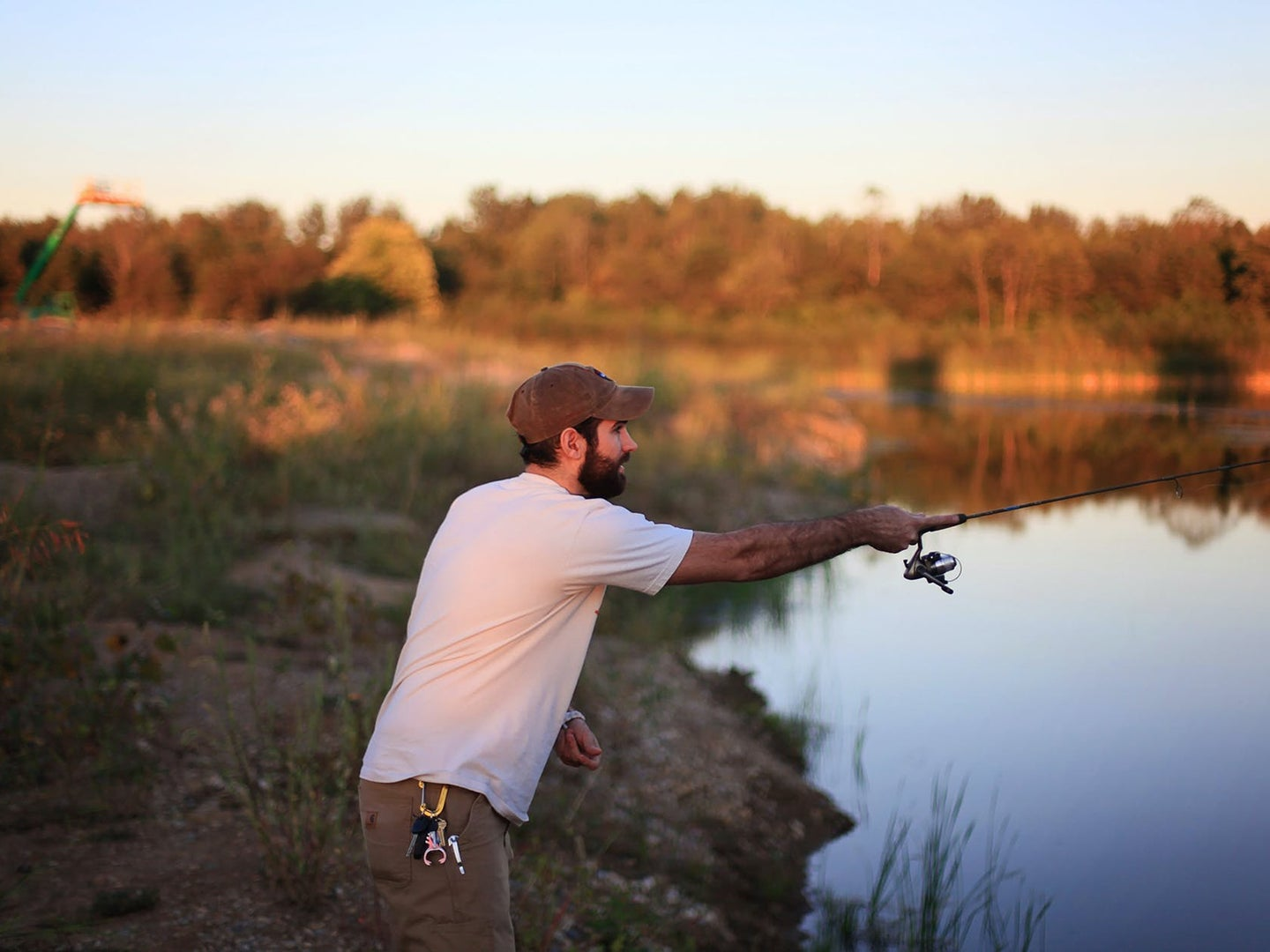 man casting out fishing rod