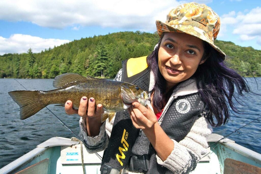 Female angler holding a smallmouth bass.