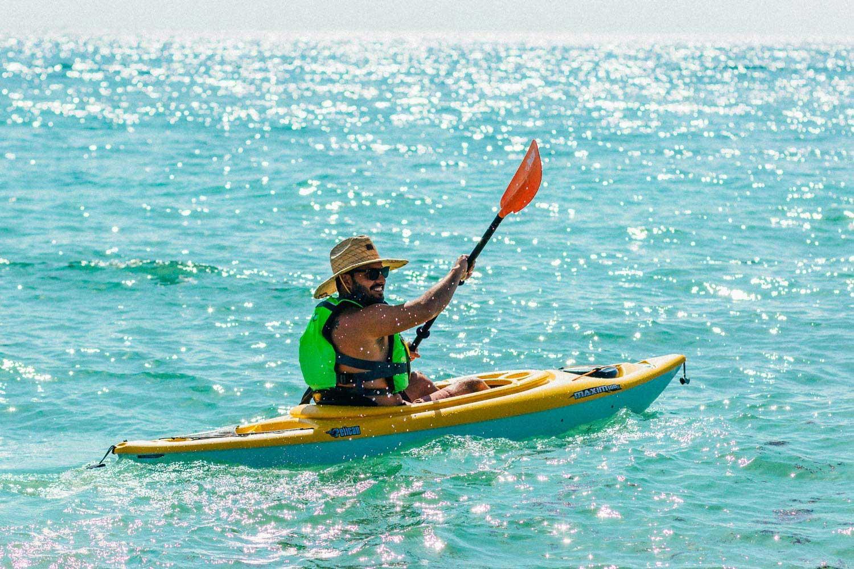 Man in the ocean paddling a kayak